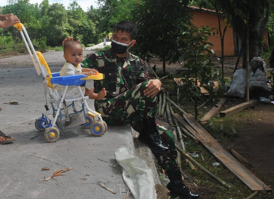 Anak-Anak Bercengkrama Bersama Anggota satgas Di Jalan Yang Sudah Mulus
